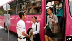 Cambodian passengers disembark from a bus as Phnom Penh begins its trial for public bus service, Wednesday, Feb. 5, 2014, in Phnom Penh, Cambodia.