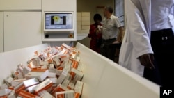 A newly mechanized pharmaceutical machine that helps pharmacists dispense medicine is loaded with ARV medication, at the U.S. sponsored Themba Lethu, HIV/AIDS Clinic, at the Helen Joseph hospital, in Johannesburg, South Africa, Nov. 15, 2012.