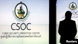 FILE - A man is silhouetted against a screen at the Cyber Security Operation Center in Bangkok.