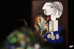 "Pablo Picasso is one of the most famous Cubist painters. Here, a woman looks at his painting titled ""Nature Morte Aux Tulipes"" at an auction in Hong Kong, Oct. 2012."