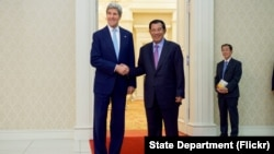 U.S. Secretary of State John Kerry poses for photographers with Cambodian Prime Minister Hun Sen before a bilateral meeting on Jan. 26, 2016, at the Peace Palace in Phnom Penh, Cambodia.