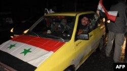 Seorang pengemudi taksi memasang dan melambaikan bendera Suriah untuk merayakan kemenangan pasukan pemerintah di jalanan kota Aleppo (22/12). (AFP/George Ourfalian)