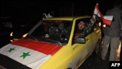 A Syrian driver flies a national flag as people celebrate in the streets in Aleppo, Syria, after the army said it had retaken full control of the city, Dec. 22, 2016. The victory against opposition forces was the army's biggest since the civil war erupted in 2011.