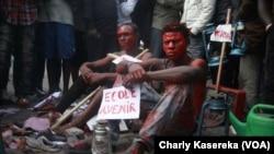 Quatre artistes-peintres, dont les visages étaient enduits de peinture rouge, ont été arrêtés à Goma, Nord-Kivu, 23 juin 2017. (VOA/Charly Kasereka)