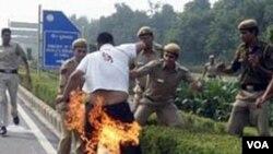 Polisi India memadamkan api di tubuh Sherab TseDor, warga Tibet di New Delhi, yang melakukan aksi protes di depan Kedutaan Tiongkok, New Delhi, Jumat (4/11)