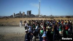 Miners chant slogans as they march past the Lonmin mine during the one-year anniversary commemorations to mark the killings of 34 striking platinum miners shot dead by police outside the Marikana platinum mine in Rustenburg, Aug. 16, 2013.