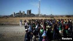 FILE - Miners chant slogans as they march past the Lonmin mine during the one-year anniversary commemorations to mark the killings of 34 striking platinum miners shot dead by police outside the Marikana platinum mine in Rustenburg, South Africa on Aug. 16, 2013.