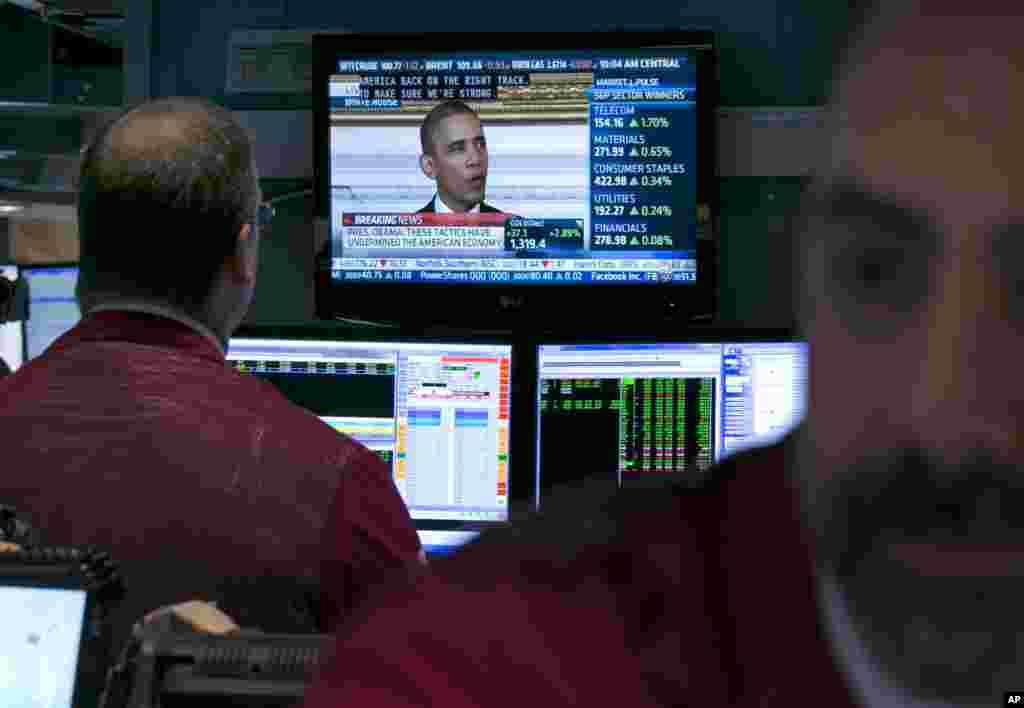 New York Borsası çalışanları televizyonda konuşma yapan Başkan Obama'yı izliyor