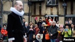 Tourists watch actors perform at the house where William Shakespeare was born during celebrations to mark the 400th anniversary of the playwright's death in Stratford-Upon-Avon, England, April 23, 2016.