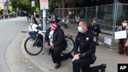 Le chef de police Andy Mills, à droite, et le maire de Santa Cruz Justin Cummings, au centre, mettent un genou à terre sur Pacific Avenue au centre-ville de Santa Cruz en Californie le 30 mai 2020 pour honorer la mémoire de George Floyd.