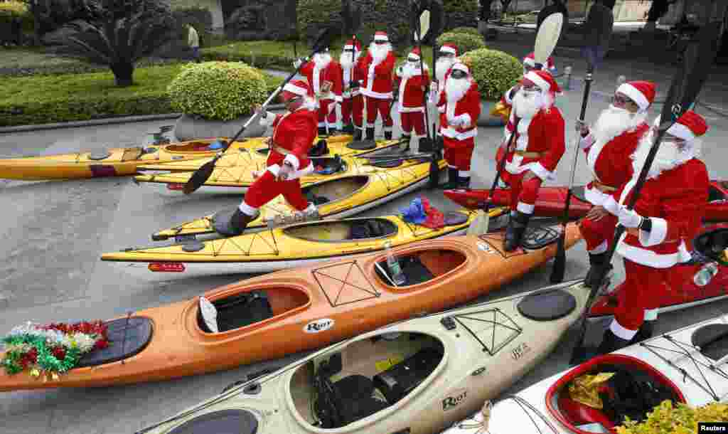 Members of a local kayak club dressed as Santa Claus prepare to take their kayaks into Zhujiang River in Guangzhou, Guangdong province, China, Dec. 25, 2013.