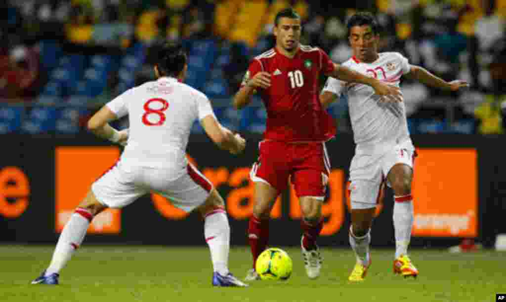 Morocco's El Ahmadi Aroussi dribbles the ball past Tunisia's Korbi Khaled and Allagui Sami during their African Cup of Nations Group C soccer at Stade De L'Amitie Stadium in Libreville