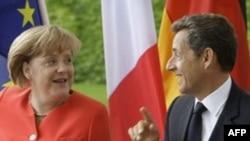 Tổng thống Pháp Nicolas Sarkozy (phải) và Thủ tướng Ðức Chancellor Angela Merkel thảo luận trước khi tới dự cuộc họp ở Berlin, Ðức, ngày 17/6/2011