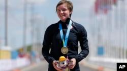 Archivo - En esta foto del 22 de julio de 2015 se ve a la medallista de oro de EE.UU., Kelly Catlin tras ganar la competencia femenina individual de ciclismo en los Juegos Panamericanos en Milton, Ontario, Canadá.