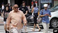 Seorang pria menyeberang jalan di Washington sambil mengetik pesan teks di ponselnya (Foto: dok/ AP Photo/Pablo Martinez Monsivais)