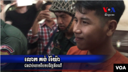 Kong Raiya is escorted by police officers after the Municipal Court of Phnom Penh sentenced him to one and a half year in prison, on March 15, 2016 for a Facebook post calling for a regime change. (Pin Sisovann/ VOA Khmer)