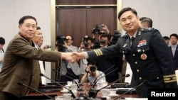 North Korean Lieutenant General An Ik San shakes hands with South Korean Major General Kim Do-gyun during a meeting at the Peace House of the border village of Panmunjom, South Korea, July 31, 2018.