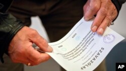 Một người đàn ông cầm lá phiếu phản đối chính sách di cư của Thủ tướng Hungary Viktor Orban trong cuộc trưng cầu dân ý Budapest, ngày 2 tháng 10 năm 2016.