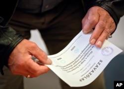 2016年10月2日,一个男子在布达佩斯他手持一张公投选票。票上显示,他投的是反对票。