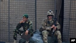 FILE - In this Aug. 5, 2015 photo, an Afghan National Army soldier, left, smokes as a U.S. Army soldier from Charlie Company, 2-14 Infantry Regiment, 2nd Brigade, 10th Mountain Division sits next to him in Camp Khogyani in Nangarhar province, east of Kabul, Afghanistan.