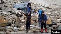 25일 시리아 알레포 북부 알라이 마을 어린이들이 내전으로 부서진 건물 잔해 주변에서 놀고 있다.