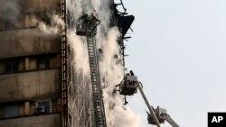 19일 이란 수도 테헤란의 17층짜리 상가건물에 화재가 발생해 소방관들이 진화 작업을 하고 있다.