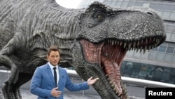 Cast member Chris Pratt poses in front of a model dinosaur while promoting the forthcoming film 'Jurassic World: Fallen Kingdom' in London, May 24, 2018.