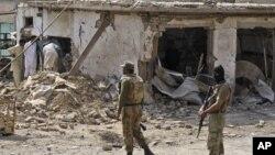 Warga memeriksa lokasi tempat meledaknya bom dalam serangan di Darra Adam Khel, propinsi Khyber Pakhtunkhwa perbatasan Afghanistan (13/10).