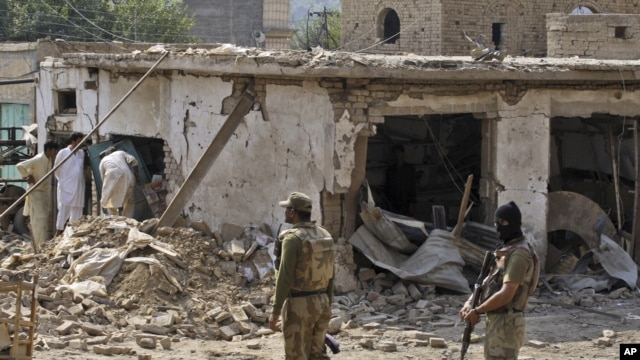 Pakistani men check the damage caused by a car bomb explosion at the site in the town of Darra Adam Khel in the troubled Khyber Pakhtunkhwa province bordering Afghanistan, October 13, 2012.