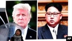 Žena sa kišobranom prolazi ispred ogromnog ekrana u Tokiju, na kojem se vide američki predsednik Donald Tramp i severnokorejski lider Kim Džong Un (Foto: Koji Sasahara/AP)