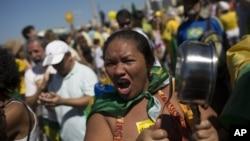 ແມ່ຍິງຄົນໜຶ່ງຮ້ອງຄຳຂວັນພ້ອມທັງຕີໝໍ້ ໃນລະຫວ່າງການປະທ້ວງຕໍ່ຕ້ານລັດຖະບານ ຮຽກຮ້ອງໃຫ້ປົດຕ່ຳແໜ່ງປະທານາທິບໍດີ ບຣາຊິລ Dilma Rousseff ໃນນະຄອນຫຼວງ Rio de Janeiro. 16 ສິງຫາ, 2015.