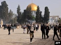Warga Palestina menyelamatkan diri dari gas air mata yang ditembakkan oleh pasukan keamanan Israel di kompleks masjid Al-Aqsa Yerusalem, 10 Mei 2021, menjelang pawai yang direncanakan untuk memperingati pengambilalihan Israel atas Yerusalem dalam Perang Enam Hari 1967. (AFP/Ahmad Gharabli)