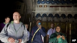 A Nigerian tourist, center, takes a picture as he exits the Church of the Holy Sepulcher, the site traditionally believed by Christians to be the tomb of Jesus, in Jerusalem's Old City, 27 Dec 2010