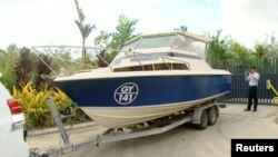 An officer takes pictures of a boat, which Australian police have seized in Cairns, Queensland, Australia in this still image taken from video, May 11, 2016.