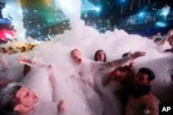 Spring Breakers are covered in foam at The City nightclub in the city of Cancun, Mexico, early Monday, March 16, 2015. Cancun continues to be one of the top foreign destinations for U.S. college students to spend Spring Break. (AP Photo)