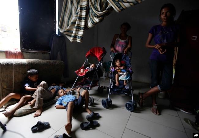 En esta foto del 27 de junio de 2018, algunas madres vigilan a niños venezolanos mientras otros trabajan, dentro de una casa escasamente amueblada compartida por unas 10 personas en Cúcuta, Colombia.