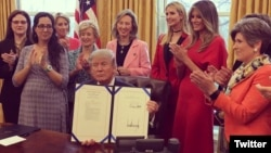President Donald Trump at the White House, signing two laws that authorize NASA and the National Science Foundation to encourage women and girls to get into STEM fields.