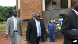 Elton Mangoma, center, Zimbabwe's Minster of Energy and Power Development outside the magistrates courts, accompanied by two unidentified police detectives in Harare, March, 11, 2011.