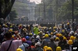 Pengunjuk rasa anti kudeta, di balik barikade darurat, berhadapan dengan aparat keamanan Myanmar di Yangon, Myanmar, Selasa 2 Maret 2021.