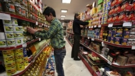 Mohammad Kouhi, left, and Hassan Akbarzadeh, work, in a supermarket in Tehran, Iran, January 23, 2013.