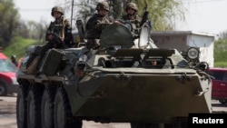 Pasukan keamanan Ukraina mengendarai tank di pos pemeriksaan dekat Slovyansk di bagian timur Ukraina, 4 Mei 2014.
