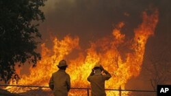 Firefighters from around the state battle a large wildfire on Highway 71 near Smithville, Texas. A roaring wildfire raced unchecked Monday through rain-starved farm and ranchland in Texas, destroying nearly 500 homes during a rapid advance fanned in part