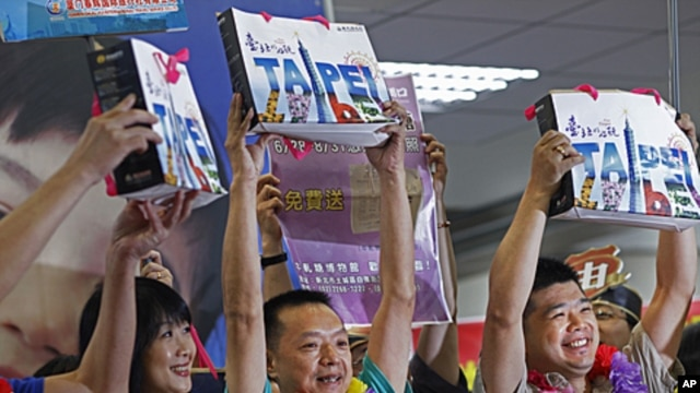 The first individual Chinese tourists hold up gift bags as they arrive at the Songshan airport in downtown Taipei, Taiwan,  June 28, 2011