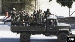 Бойцы сирийской армии передвигаются на грузовике по пригороду Дамаска
