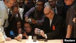 Miembros de los medios de comunicación fotografían el nuevo iPhone 5 en su presentación.