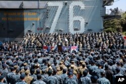 FILE - U.S. Vice President Mike Pence, center, speaks to U.S. servicemen and Japanese Self-Defense Forces personnel on the flight deck of U.S. navy nuclear-powered aircraft carrier USS Ronald Reagan, at the U.S. Navy's Yokosuka base in Yokosuka, south of Tokyo, April 19, 2017.