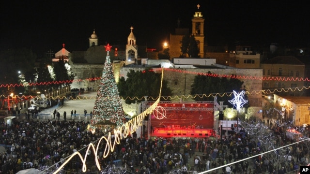 Christian worshippers and tourists celebrate at the Manger Square in front of the Church of the Nativity, in the West Bank town of Bethlehem, December 24, 2012.