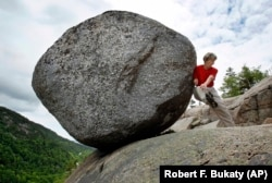 Doris Morgan, of Tampa, Fla., playfully attempts to dislodge the Bubble Rock near the summit of South Bubble Mountain, Friday, June 4, 2010, in Acadia National Park near Bar Harbor, Maine.