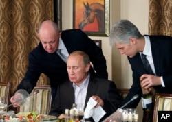FILE - Businessman Yevgeny Prigozhin, left, serves food to Russian Prime Minister Vladimir Putin, center, during dinner at Prigozhin's restaurant outside Moscow, Russia, Nov. 11, 2011.