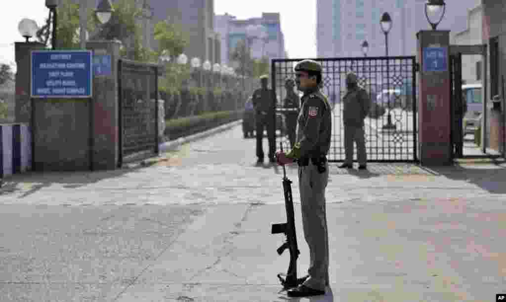 A Delhi policeman stands guard near the gate of a district court where the accused in a gang rape are undergoing trial, in New Delhi, India, January 24, 2013.